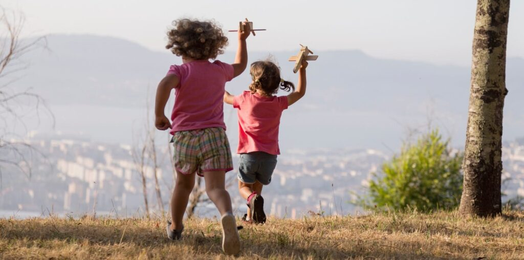 Foto de dúas nenas a xogar na natureza