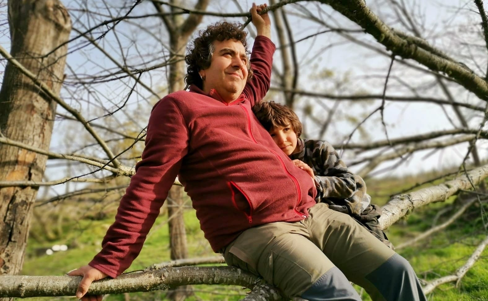 Pai e fillo subidos abrazados a unha árbore