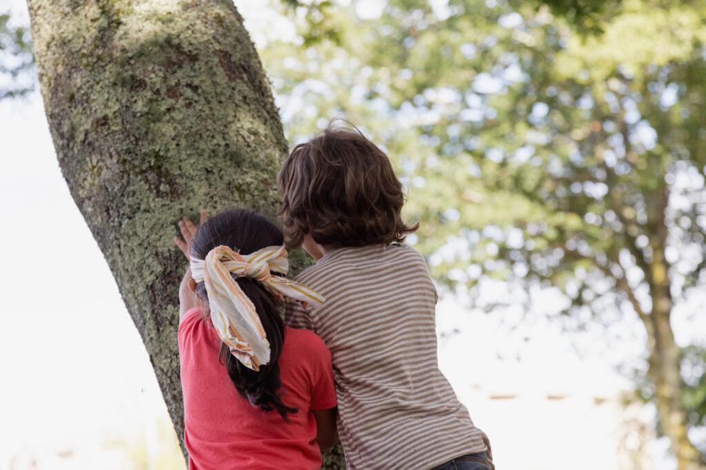 Parella de nenos abrazando unha árbore